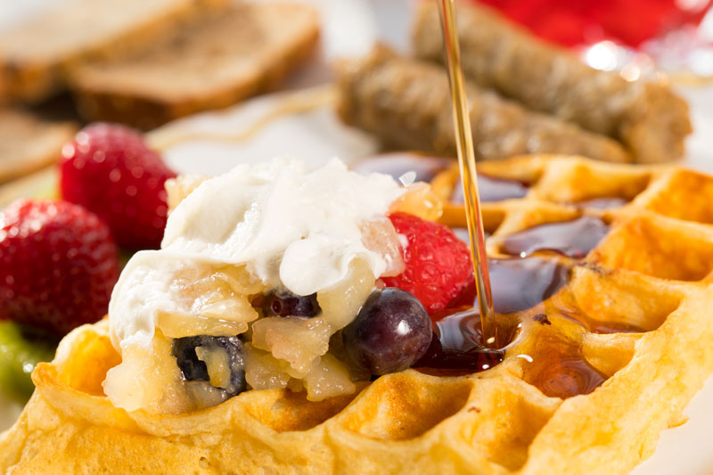 Pouring syrup on Waffle with fruit compote and whipped cream