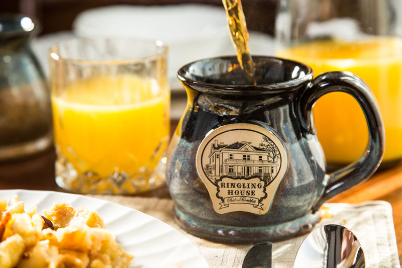Pouring coffee in Ringling House Mug and Juice in crystal glass